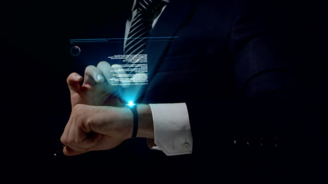 businessman using smartwatch. touching holographic screen - holographic stock videos and b-roll footage