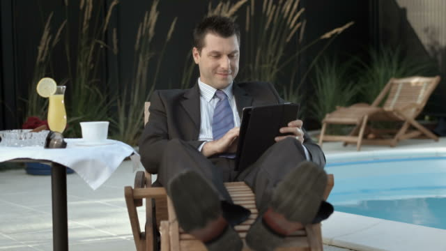 hd dolly: businessman using tablet by the pool - outdoor chair stock videos & royalty-free footage