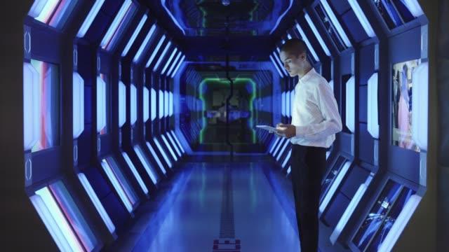 vídeos y material grabado en eventos de stock de businessman using tablet pc in spaceship corridor - pasillo característica de edificio
