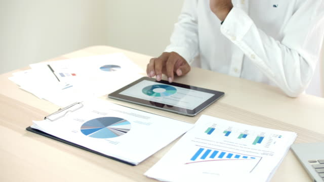Businessman using tablet to Analyzing Graph with document on the table , slow motion