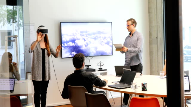 Businessman using VR headset while giving presentation in meeting