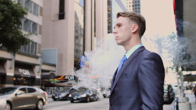 businessman vaping on busy street - necktie stock videos & royalty-free footage