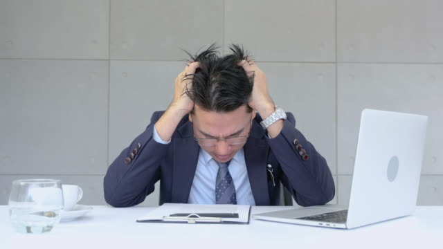 Businessman very stressed out about paperwork and data on laptop in modern office.