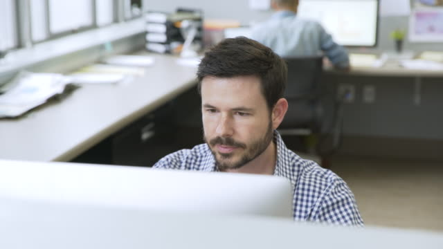 businessman video chatting in startup office - プレイドシャツ点の映像素材/bロール