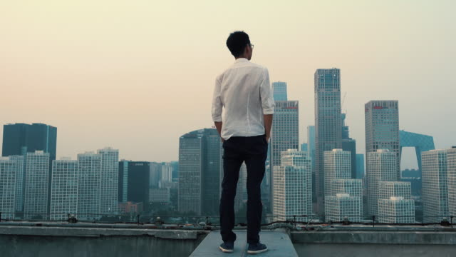 businessman viewing city from rooftop - 立つ点の映像素材/bロール