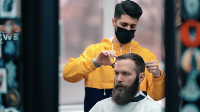 vídeos de stock, filmes e b-roll de empresário visita ndo o barbeiro durante o covid-19 - salão de beleza