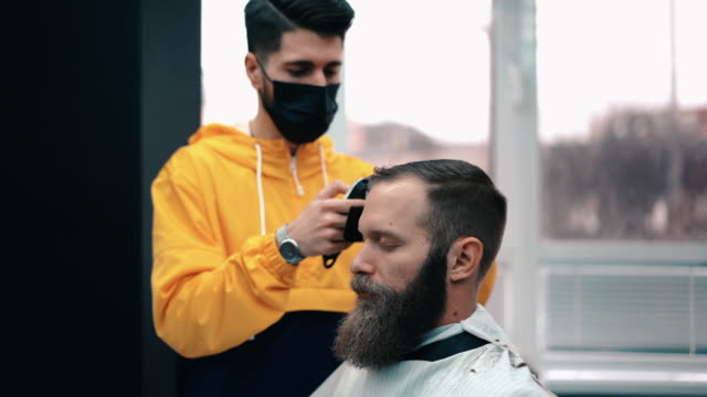 businessman visiting the barber shop during covid-19 - cutting hair stock videos & royalty-free footage