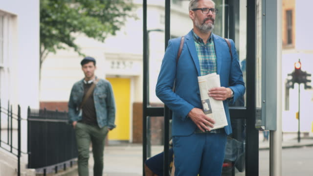 businessman waiting at bus stop - bushaltestelle stock-videos und b-roll-filmmaterial