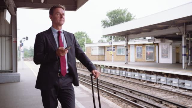 Businessman waiting for delayed train on platform