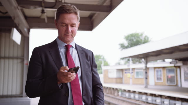 Businessman waiting for delayed train on platform