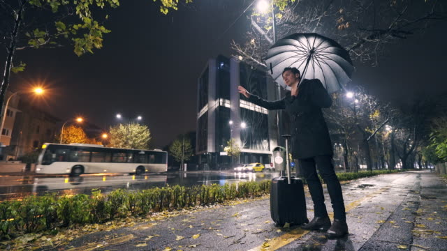 Businessman waiting for taxi or uber in the rain.