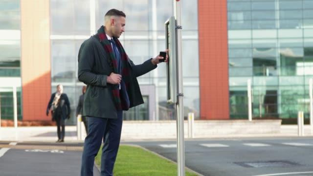 バスを待っているビジネスマン - バス停留所点の映像素材/bロール