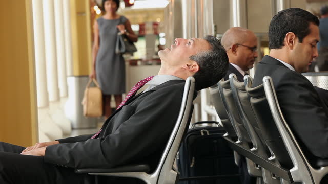 businessman waiting in airport lounge - aspettare video stock e b–roll