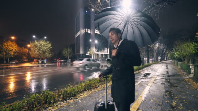 businessman waiting in the rain. - taxi video stock e b–roll