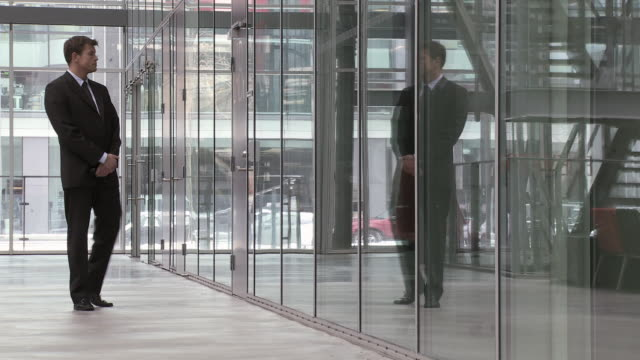 ms businessman waiting outside glass office door, copenhagen, denmark - kompletter anzug stock-videos und b-roll-filmmaterial