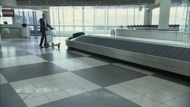 WS Businessman waiting with luggage cart near empty airport baggage claim carousel / Munich, Germany