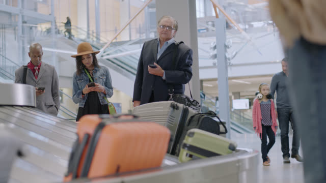 businessman waits anxiously for luggage at baggage claim in airport terminal. - luggage stock videos & royalty-free footage