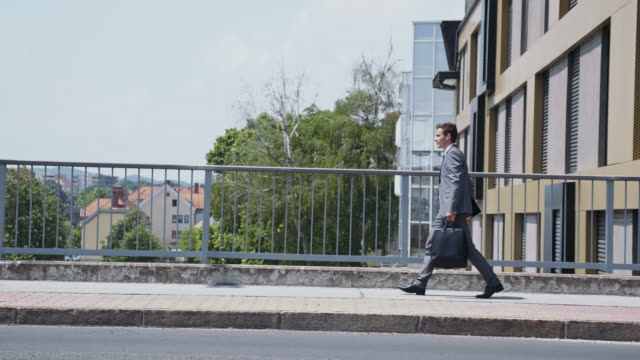 businessman walking across the bridge in city - carrying stock videos & royalty-free footage