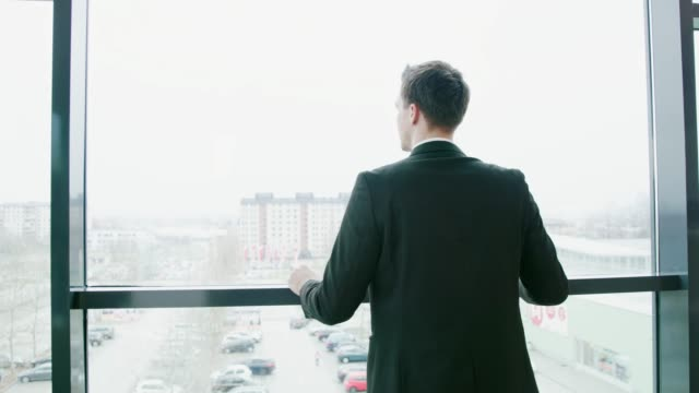businessman walking and stopping at office window, real time - looking at view stock videos & royalty-free footage