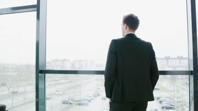 Geschäftsmann zu Fuß und hält am Bürofenster, Real-time