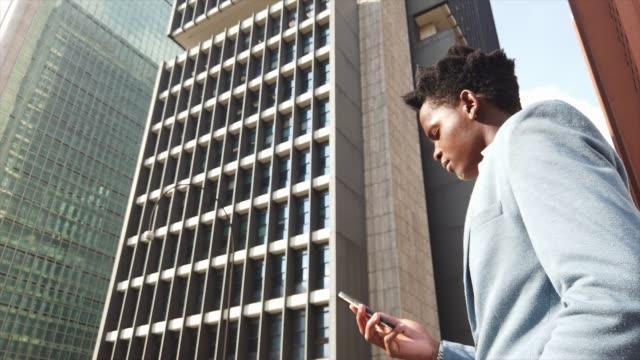 vídeos de stock, filmes e b-roll de homem de negócios que anda e que usa o móbil em movimento - foco técnica de imagem