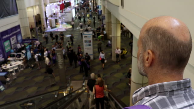 businessman walking around convention hall - balding stock videos and b-roll footage