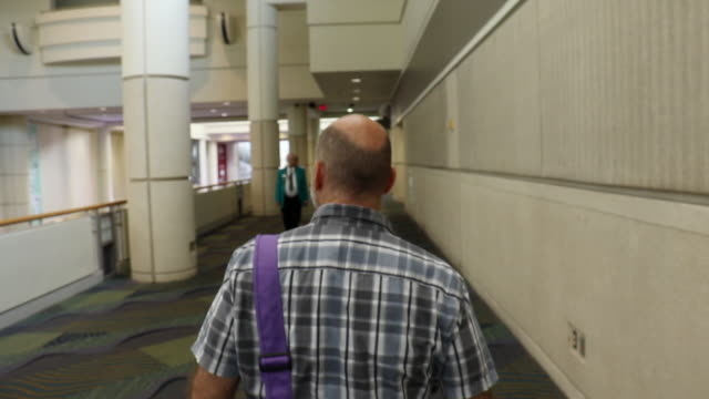 businessman walking around convention hall - following stock videos & royalty-free footage