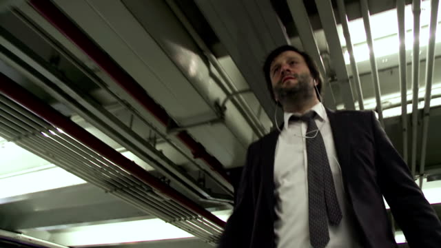 hd: businessman walking down a parking garage - full suit stock videos and b-roll footage