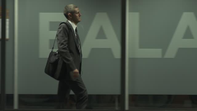 ms pan businessman walking down 'balance' corridor, chicago, illinois, usa - side view stock videos & royalty-free footage