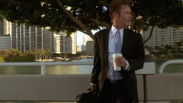 MS PAN SLO MO Businessman walking holding briefcase and coffee cup, looking back over shoulder / Miami Beach, Florida, USA
