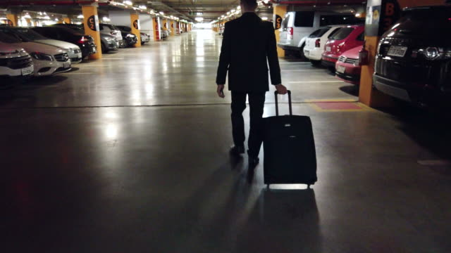 businessman walking in a garage. - car park stock videos & royalty-free footage