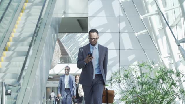 vidéos et rushes de businessman walking in airport and text messaging - voyage d'affaires