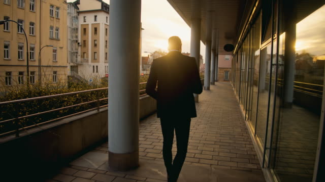ms ts businessman walking in city at sunset - wide shot stock videos & royalty-free footage