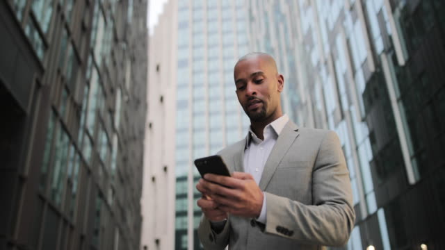 businessman walking in city using smartphone - looking up stock videos & royalty-free footage