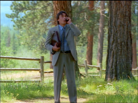 businessman walking in forest + talking on cell phone / gets excited and celebrates / montana - anno 1997 video stock e b–roll