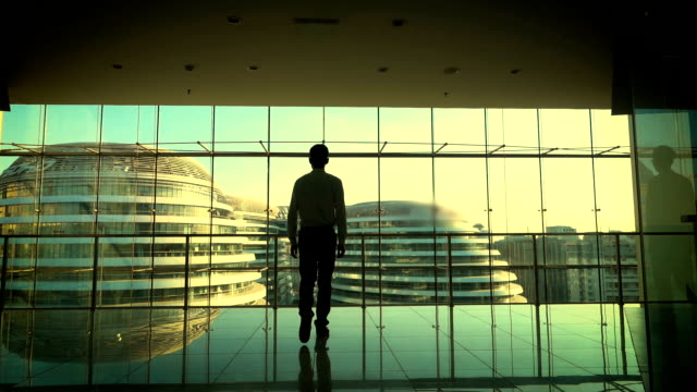 Businessman walking in office building,looking out of window
