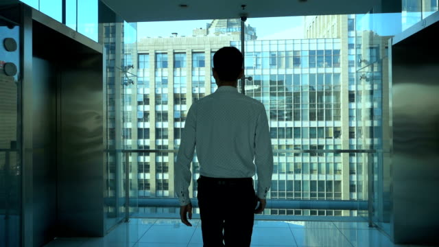 stockvideo's en b-roll-footage met businessman walking in office building,looking out of window - gang