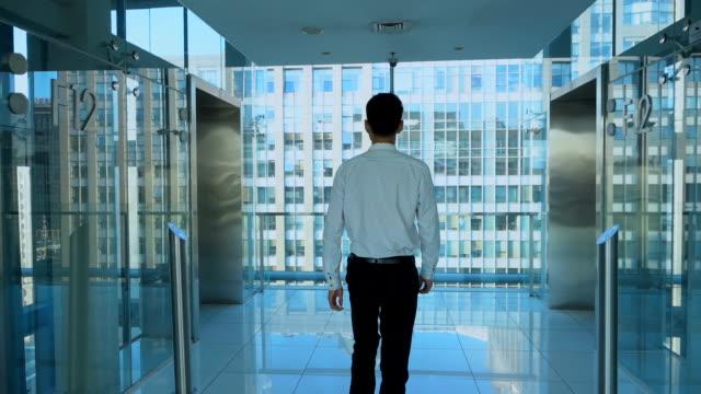 Businessman walking in office corridor