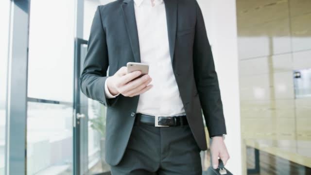 vídeos de stock, filmes e b-roll de empresário andando no escritório, em tempo real - chegada