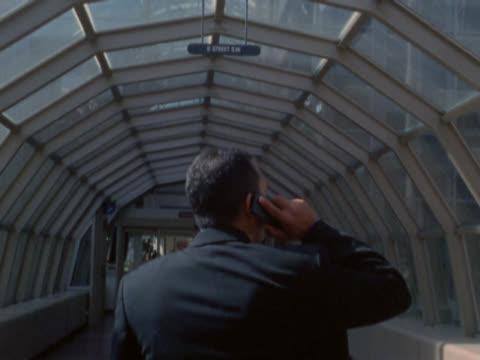 businessman walking in skybridge talking on cell phone - überdachte brücke brücke stock-videos und b-roll-filmmaterial