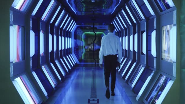 vídeos de stock e filmes b-roll de businessman walking in spaceship style corridor - nave espacial