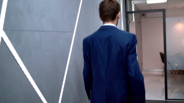 vidéos et rushes de l'homme d'affaires marchant dans le couloir de bureau réalise qu'il a oublié quelque chose pour la réunion - seulement des jeunes hommes