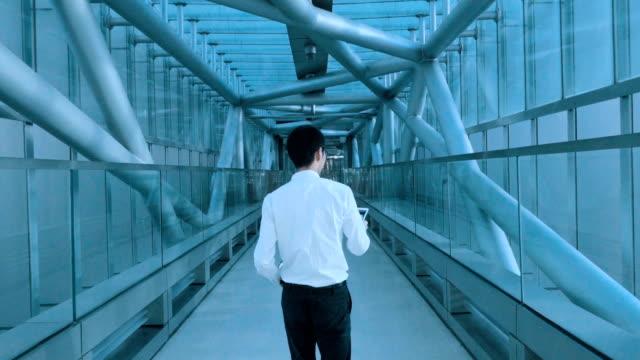 デジタル タブレットとトンネルを歩くビジネスマン - 下を向く点の映像素材/bロール