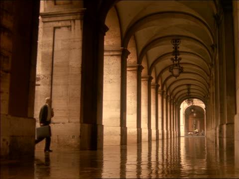stockvideo's en b-roll-footage met businessman walking into building under porticos / praca do comercio, lisbon - alleen één oudere man
