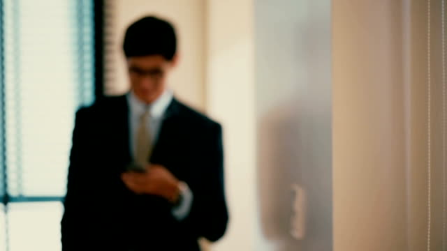 Businessman Walking on Hallway  And Using Mobile Phone