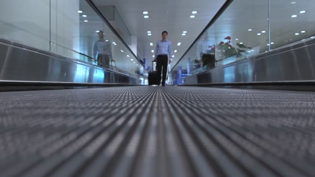 businessman walking on moving walkway in airport - diminishing perspective stock videos & royalty-free footage