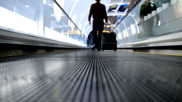 businessman walking on moving walkway - one mid adult man only stock videos & royalty-free footage