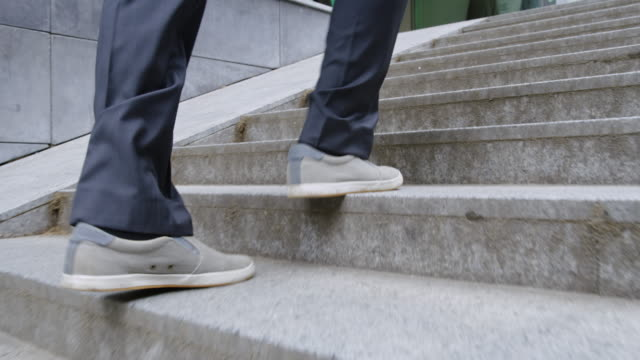 slo mo businessman walking out of underpass - human limb stock videos & royalty-free footage
