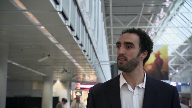 stockvideo's en b-roll-footage met ms ts businessman walking past gift shop in airport / munich, germany - münchen vliegveld