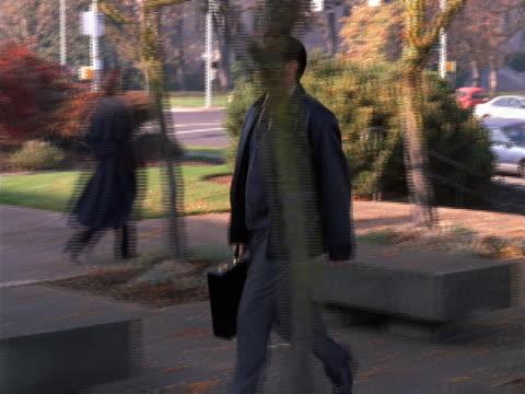 vidéos et rushes de businessman walking through a courtyard - un seul homme d'âge moyen